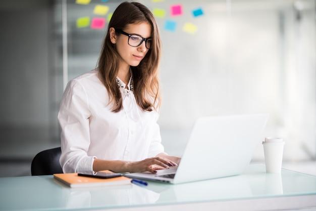 Erfolgreiche geschäftsfrau, die an laptop in ihrem büro arbeitet, gekleidet in weiße kleidung
