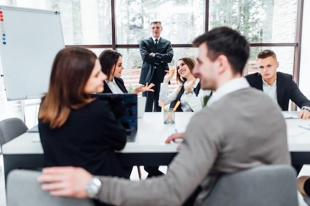 Erfolgreiche geschäftsfrau, die beim teamtraining fragen stellt, der chef hört einen vorschlag.