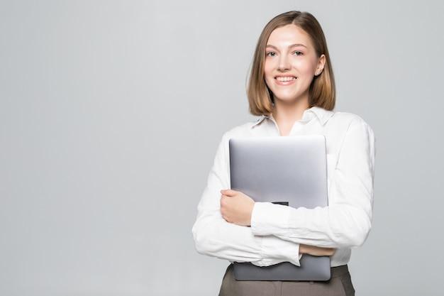 Erfolgreiche geschäftsfrau, die einen laptop über weiß hält
