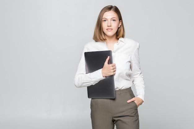 Erfolgreiche geschäftsfrau, die einen laptop über weißer wand hält