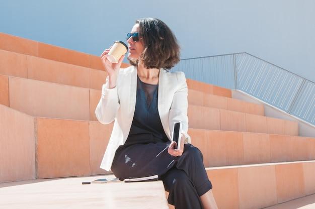 Erfolgreiche geschäftsfrau, die geschmackvollen kaffee genießt