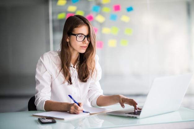 Erfolgreiche geschäftsfrau, die hart am laptop in ihrem büro arbeitet, gekleidet in weiße kleidung