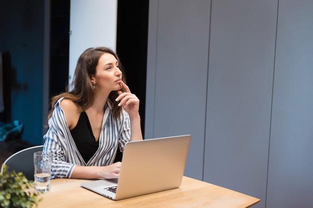 Erfolgreiche geschäftsfrau, die sehr nachdenklich aussieht, während sie mit geöffnetem laptop in einem modernen büro sitzt