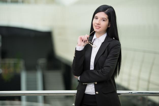Erfolgreiche geschäftsfrau, die überzeugt und das lächeln schaut