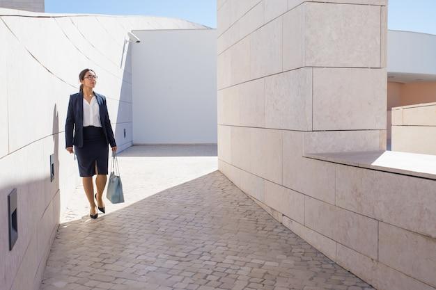 Erfolgreiche geschäftsfrau, die um modernes geschäftszentrum geht