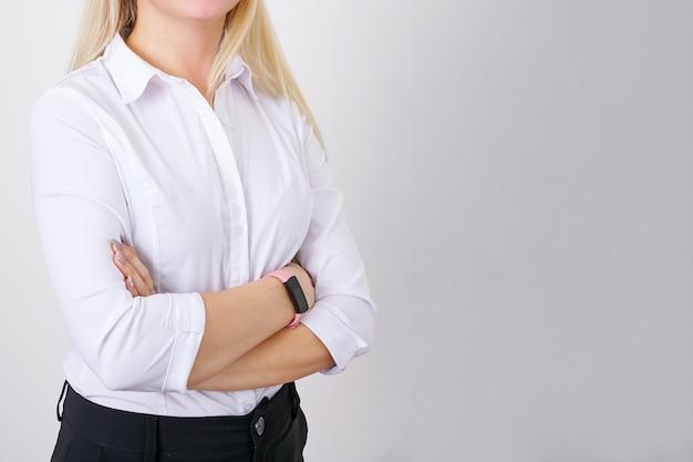 Erfolgreiche geschäftsfrau kaukasischer abstammung mit gefalteten händen, kein gesicht, weißes hemd auf hellem rücken...