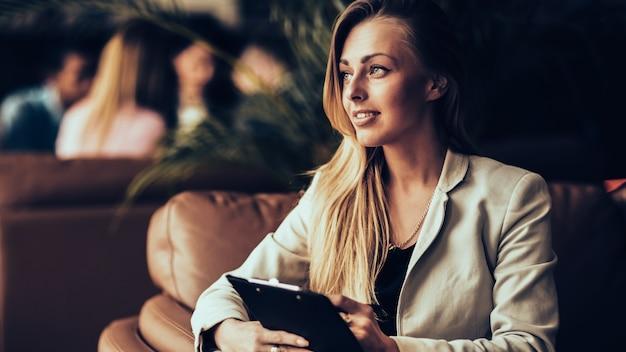 Erfolgreiche geschäftsfrau mit dokumenten, die in einem stuhl in a . sitzen