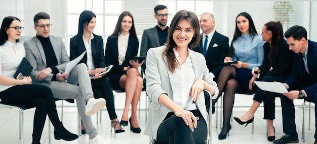 Erfolgreiche geschäftsfrau und eine gruppe führender experten im konferenzraum