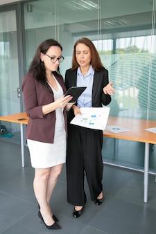 Erfolgreiche geschäftsfrauen diskutieren, betrachten tablet-bildschirm und stehen im konferenzraum