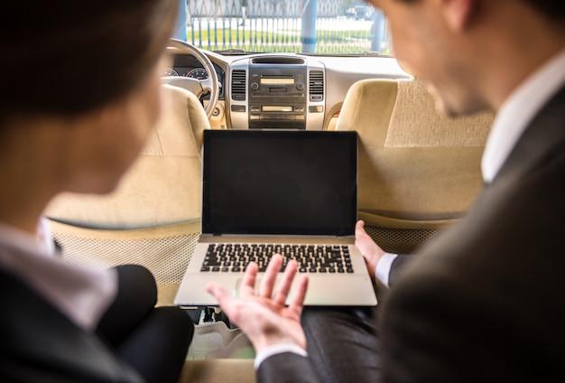 Erfolgreiche geschäftsleute bei einer besprechung im auto sitzen.