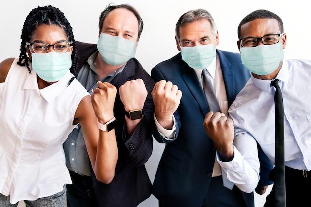 Erfolgreiche geschäftsleute, die gesichtsmasken bei der arbeit tragen