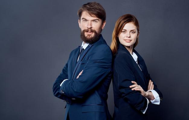 Erfolgreiche geschäftsleute in anzügen stehen mit dem rücken zueinander auf einem selbstbewussten grauen hintergrund. hochwertiges foto