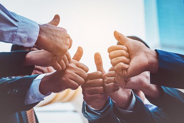 Erfolgreiche geschäftsleute mit daumen hoch und lächelnd, business-team