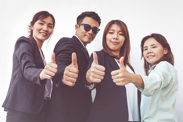Erfolgreiche geschäftsleute mit den daumen oben und dem lächeln, geschäftsteam