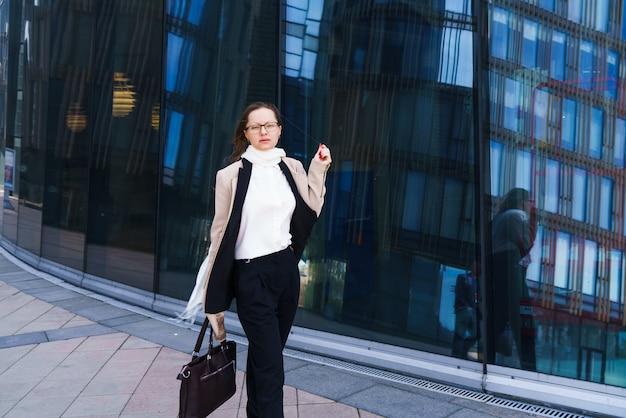 Erfolgreiche glückliche geschäftsfrau mit brille kaukasische ethnizität in stilvoller geschäftskleidung mit einem ba...