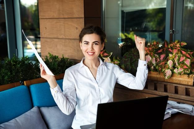 Erfolgreiche glückliche junge frau, die an laptop im café im freien arbeitet