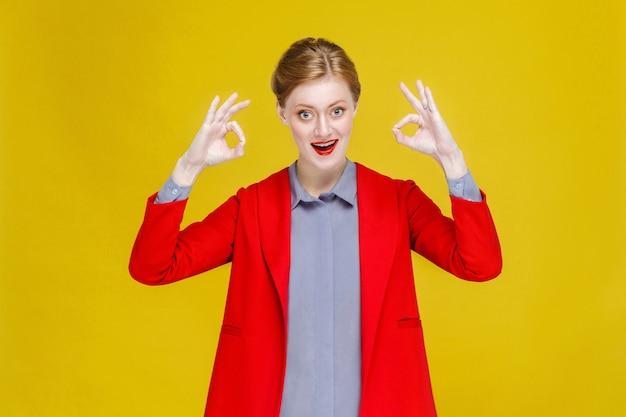 Erfolgreiche gut gekleidete rothaarige geschäftsfrau, die okayzeichen zeigt
