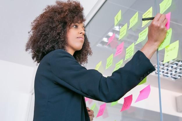 Erfolgreiche hübsche geschäftsfrau, die auf aufkleber mit marker schreibt. nachdenkliche, selbstbewusste, lockige managerin, die ihre idee für das projekt teilt und sich notizen macht. brainstorming-, geschäfts- und schulungskonzept
