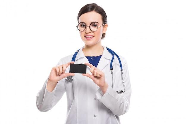 Erfolgreiche junge ärztin mit dem stethoskop, das visitenkarte in der weißen uniform zeigt