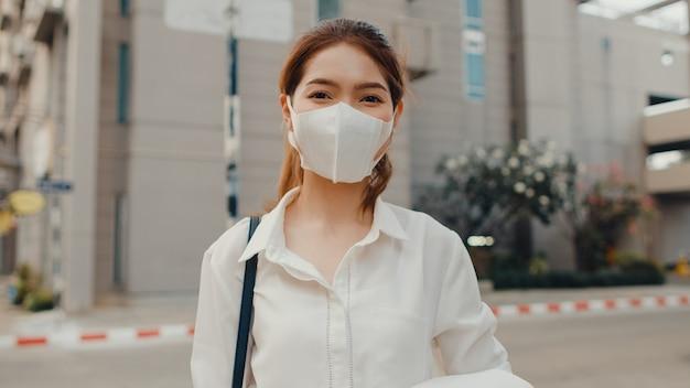 Erfolgreiche junge asiatische geschäftsfrau in modebürokleidung, die medizinische gesichtsmaske trägt, die in der straße lächelt