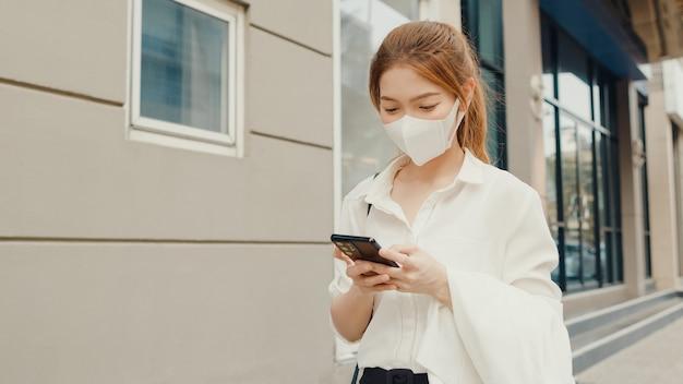 Erfolgreiche junge asiatische geschäftsfrau in modebürokleidung, die medizinische gesichtsmaske unter verwendung des smartphones trägt