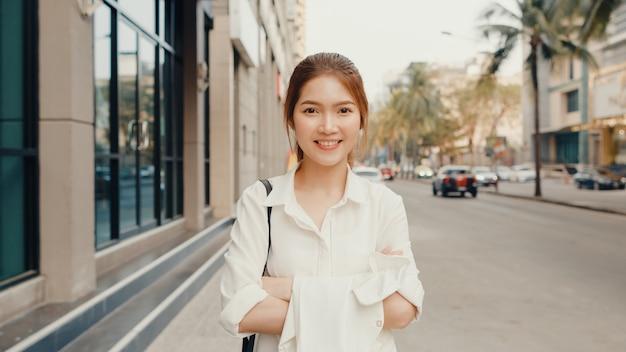 Erfolgreiche junge asiatische geschäftsfrau in modebürokleidung lächelnd, während glücklich allein auf der straße stehend