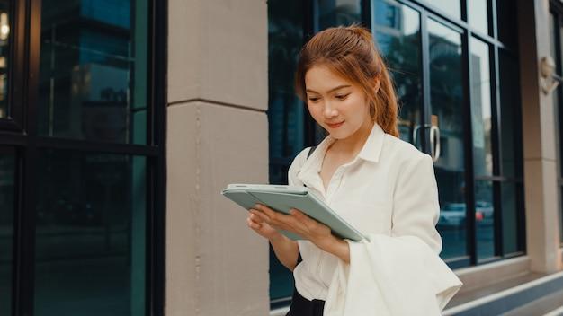Erfolgreiche junge asiatische geschäftsfrau in modebürokleidung unter verwendung des digitalen tablets und des schreibens der textnachricht