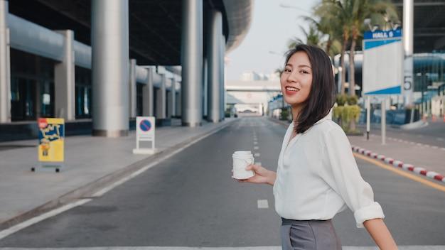Erfolgreiche junge asiatische geschäftsfrau in modischer bürokleidung, die einweg-pappbecher mit heißem getränk hält und smartphone benutzt, während sie im freien in der urbanen modernen stadt spazieren geht