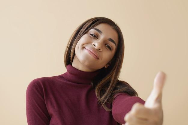 Erfolgreiche junge dunkelhäutige frau, die stilvollen rollkragenpullover trägt, positiv lächelt und daumen hoch geste zeigt