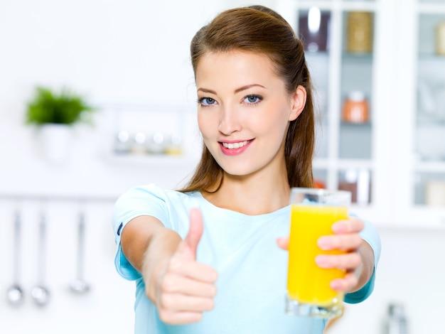 Erfolgreiche junge frau daumen hoch mit einem glas frischem orangensaft