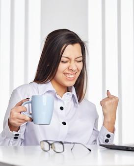 Erfolgreiche junge frau im amt, eine tasse kaffee haltend.