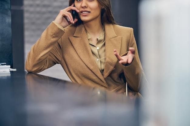 Erfolgreiche junge frau im trendigen mantel, die an der rezeption bleibt, während sie emotional auf dem handy spricht Premium Fotos