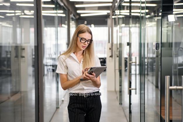Erfolgreiche junge geschäftsdame in gläsern überarbeitet firmeninformationen auf tablet-pc, während sie entlang des bürokorridors gehen.