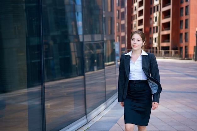 Erfolgreiche junge geschäftsfrau auf dem hintergrund eines bürogebäudes in einem schwarzen anzug