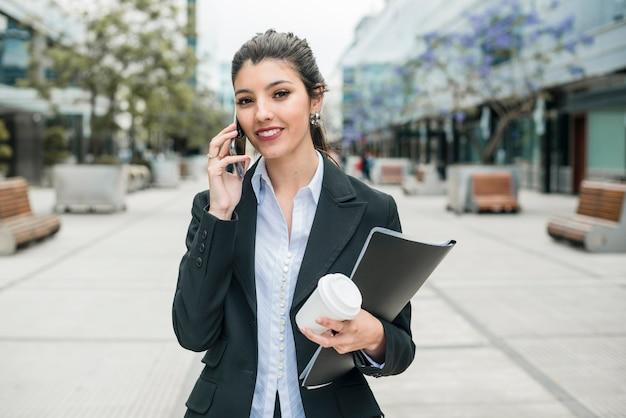 Erfolgreiche junge geschäftsfrau, die am handy in der hand wegwerfbare kaffeetasse und ordner hält