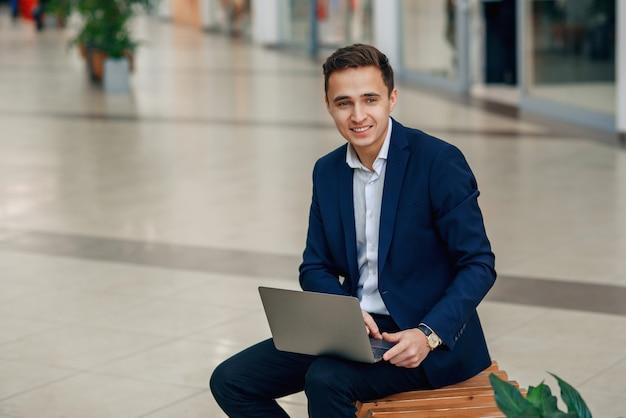 Erfolgreiche junge geschäftsfrau, die an einem laptop arbeitet, der auf einer bank sitzt