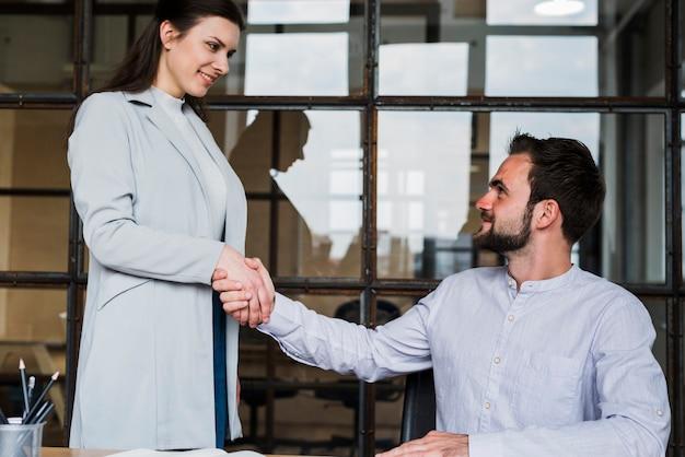 Erfolgreiche junge geschäftsfrau, die dem männlichen mitarbeiter hand rüttelt