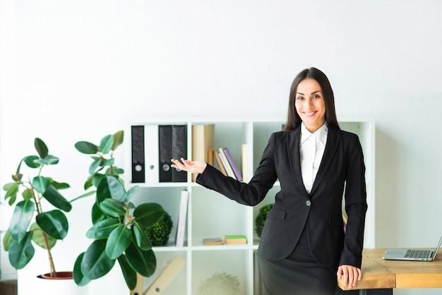 Erfolgreiche junge geschäftsfrau, die im bürodarstellen steht