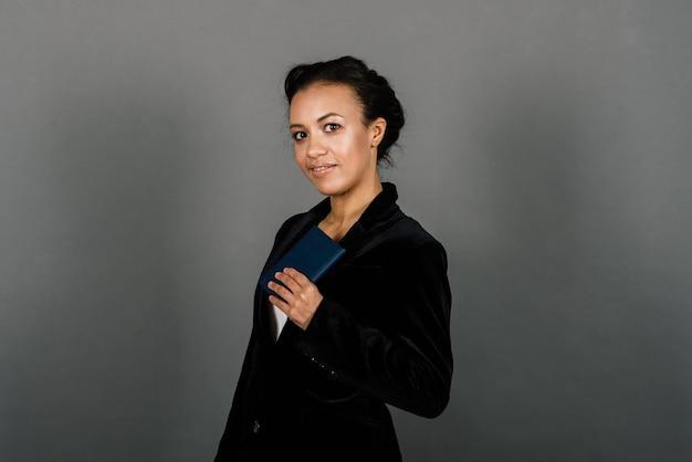 Erfolgreiche junge geschäftsfrau mit gefalteten händen, die über grauem hintergrund im studio lächeln