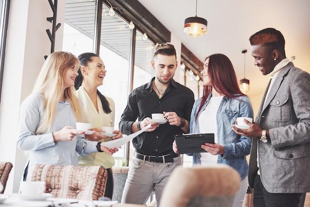 Erfolgreiche junge geschäftsleute sprechen und lächeln während der kaffeepause im büro