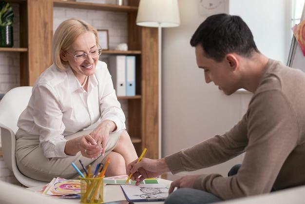Erfolgreiche kunsttherapie. fröhliche reife psychologin, die ihre beobachtung teilt, während mann malt