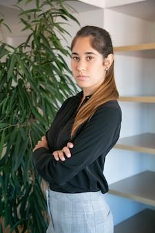 Erfolgreiche lateinische geschäftsfrau, die mit gefalteten händen steht. porträt des zuversichtlichen jungen hübschen weiblichen büroarbeitgebers in der schwarzen bluse, die bei der arbeit aufwirft. geschäfts-, unternehmens- und managementkonzept