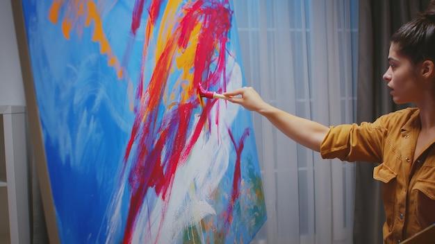 Erfolgreiche malerei der jungen frau in ihrem heimstudio.