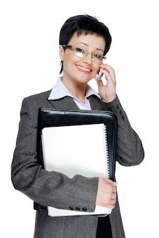 Erfolgreiche mittlere erwachsene geschäftsfrau im grauen geschäft, das durch handy spricht
