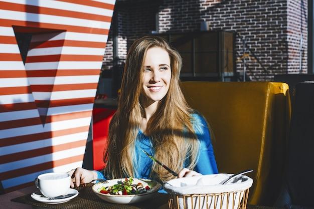 Erfolgreiche mode der schönen jungen frau und schön mit einem teller salat im restaurant