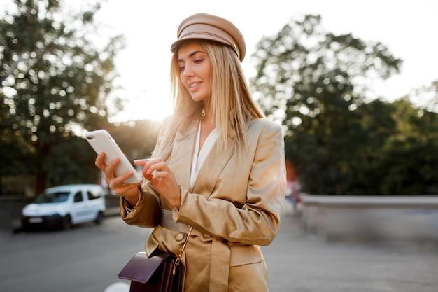 Erfolgreiche modische europäische frau im eleganten lässigen outfit, das mobyle telefon im freien aufwirft. sonnenuntergangsfarben.