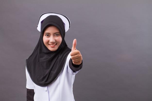 Erfolgreiche muslimische krankenschwester, die daumen aufgibt