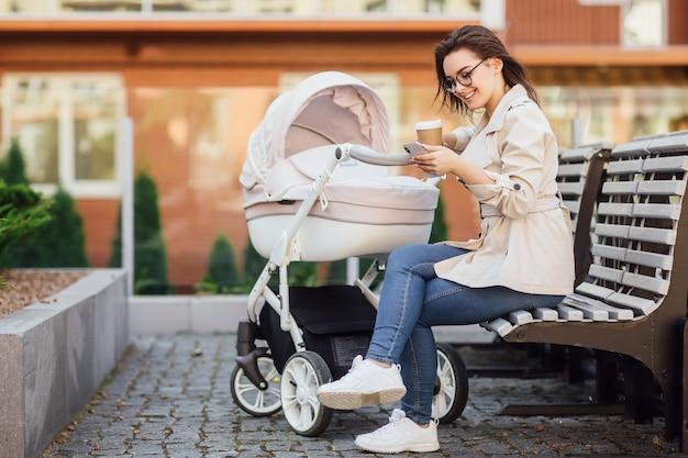 Erfolgreiche mutter mit einem neugeborenen in einem kinderwagen trinkt tee oder kaffee in einer straße in der nähe des hauses