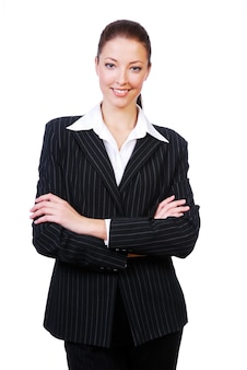 Erfolgreiche niedliche geschäftsfrau mit verschränkten armen, die auf weiß stehen