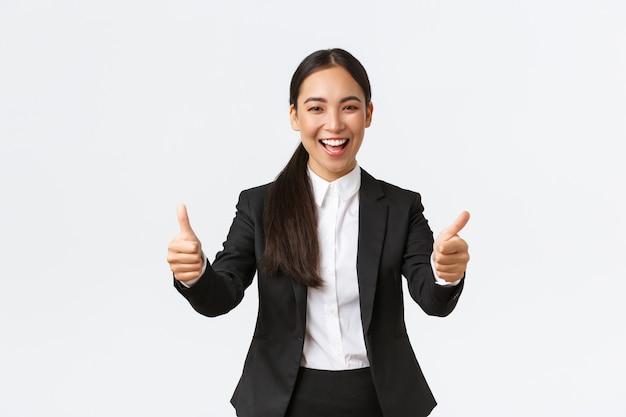 Erfolgreiche optimistische asiatische geschäftsfrau, die daumen hoch zeigt und glücklich lächelt. fröhliche managerin im business-anzug, die sich über gute nachrichten freut, gute arbeit sagt, gut gemacht oder glückwunschgeste